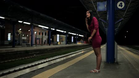 bekleme : Happy woman waiting for train going out at night with beautiful dress Stok Video