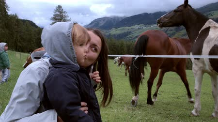 poník : Happy mother and baby daughter in front of horses