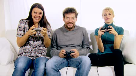 eğlence oyunları : Funny people playing with console and joystick on sofa at home