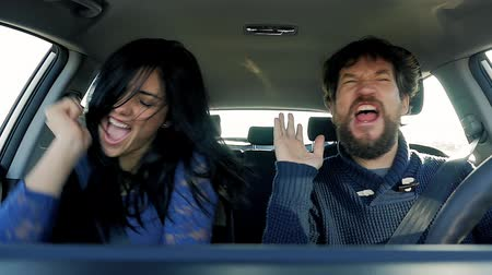 комедия : Happy beautiful woman with handsome man singing and dancing in car slow motion Стоковые видеозаписи