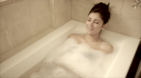 wanna : Camera moving around beautiful woman enjoying bath in tub slow motion