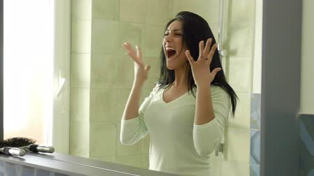 кричать : Woman screaming about messy long black hair in front of mirror slow motion