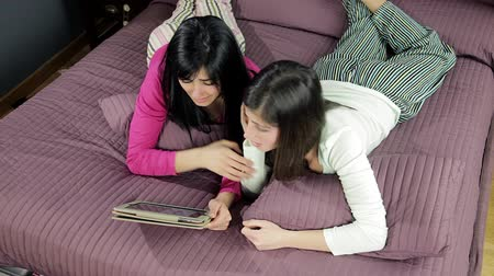 ложь : Two girlfriends looking online what to buy with tablet wide shot Стоковые видеозаписи