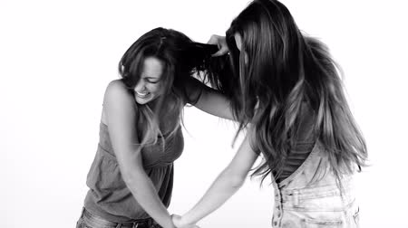 тянущий : Two girlfriends pulling long hair fighting isolated black and white