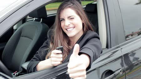 Beautiful woman showing key of new car smiling happy thumb up