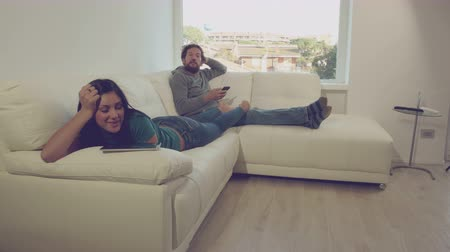 telefone celular : Man and woman lying on sofa talking using cell phone and tablet 4K