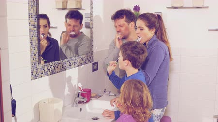 escovação : Happy family in pajamas washing teeth dancing in bathroom retro style