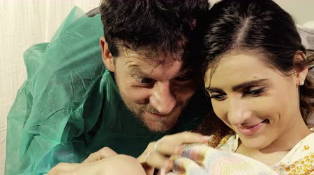 emek : Couple in love in hospital holding new born baby happy closeup