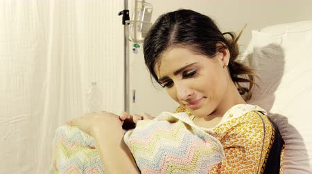 emek : Woman in hospital holding new born baby in love lying in bed