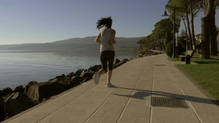 atleta : Woman jogging in front of lake slow motion shot from back dolly Stock Footage