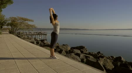 fárasztó : Woman stretching after jogging in front of lake slow motion