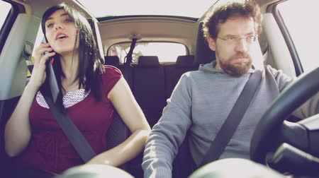 gotículas : Man in car with girlfriend angry with cell phone addiction Stock Footage