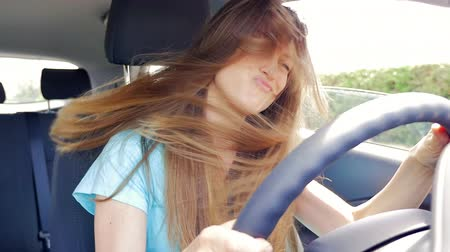amalucado : Happy woman moving long hair while driving car dancing Stock Footage
