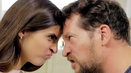 argumento : Man and woman looking at each other head to head very angry slow motion