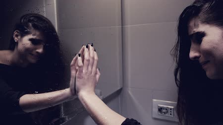 self injury : Desperate young woman in bathroom looking in mirror thinking about suicide slow motion Stock Footage