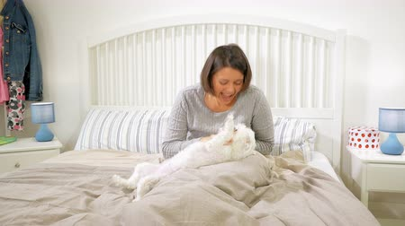 Happy woman having fun with dog in bed in the morning 4k