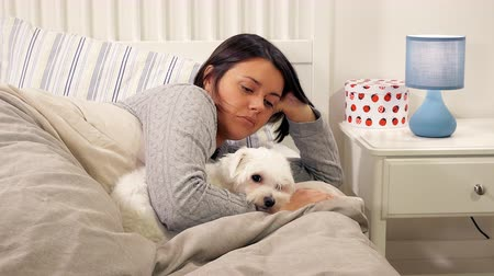 Woman at night relaxing in bed with dog cuddling and caressing