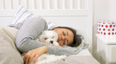 Beautiful woman waking up in the morning hugging little dog Stock Footage