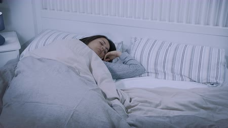 Woman sleeping in peaceful bed at night Stock Footage
