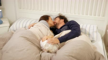 Happy couple in the morning wake up and cuddle in bed with little puppy dog