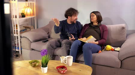 Pregnant woman unhappy about husband playing with console