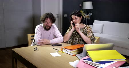 Couple at home trying to solve big problem on the phone