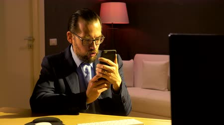 Business man recording audio message with phone in office at night Stock Footage