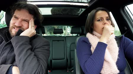 coughing : Woman in car sneezing strong while husband feels sick.