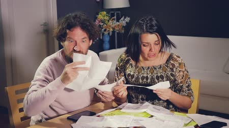 disagreement : Sad couple at home looking at night looking desperate bills