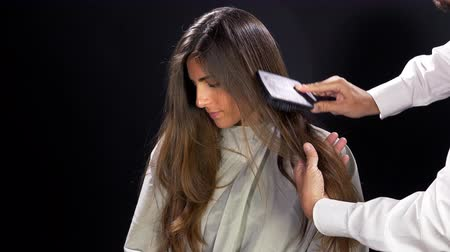 dlouhé vlasy : Hairdresser brushing long hair of client. Slow motion. Black background
