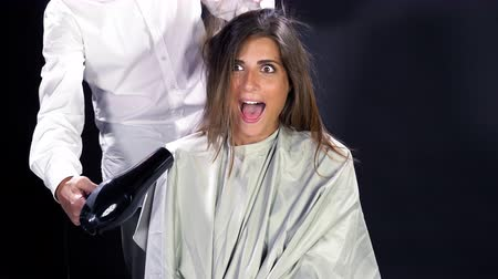 fryzjerstwo : Happy woman smiling while hairdresser is blowing her long hair.