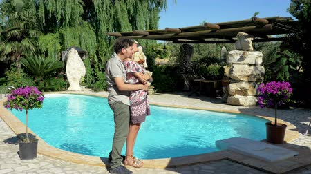 elite : Happy couple hugging in front of swimming pool