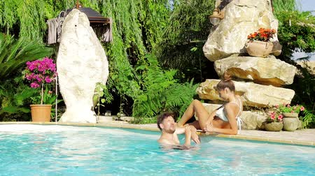 chill out : Couple chatting in a pool on vacation in luxury hotel