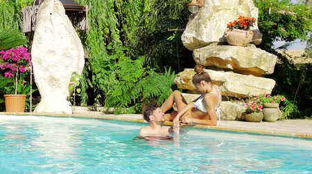 chill out : Man in love kissing hand of girlfriend in pool in hotel Stock Footage