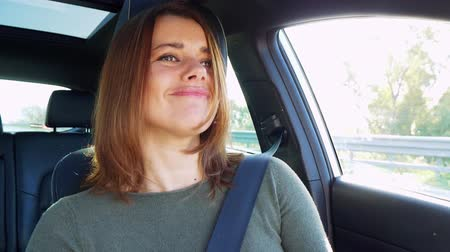 Closeup of beautiful happy woman listening to music while driving