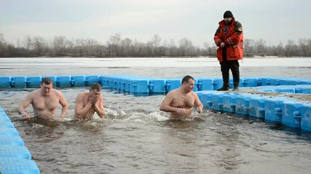 plunging : Epiphany near Svjato-Pokrovskiy Cathedral on January 19,2014 in Kiev,Ukraine.People plunging into ice-cold water as it helps body became resilient to illness. Epiphany known since 988 AD. Stock Footage