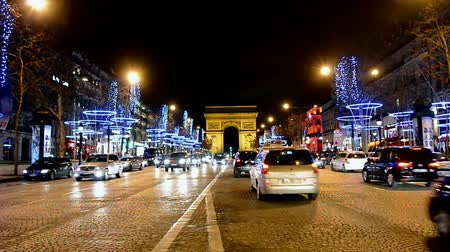 motorcar : Car traffic on Avenue des Champs-Elysees in Paris decorated with Christmas illumination in Paris, France on December 31, 2013.