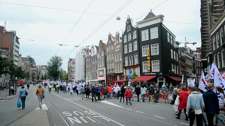 amsterodam : AMSTERDAM - SEP 12, 2015: People protest against cuts in health care sector during Red Care manifestation at the Damrak square in Amsterdam, Netherlands. 15000 people take place in the event. Dostupné videozáznamy