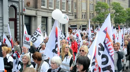 protesto : AMSTERDAM - SEP 12, 2015: People protest against cuts in health care sector during Red Care manifestation at the Damrak square in Amsterdam, Netherlands. 15000 people take place in the event. Vídeos