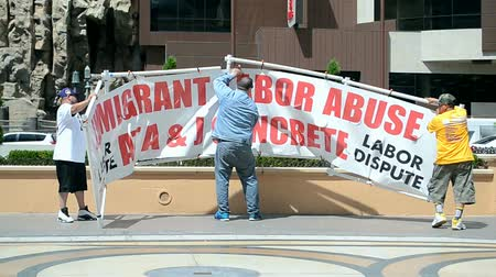 voyager : People with immigrant labor abuse placard on Las Vegas Strip on April 14, 2016 in Las Vegas, USA.The Strip has 6.8 km (4.2 mi) long with world class hotels and casinos. Stock Footage