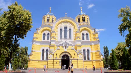 baptism : KIEV, UKRAINE - JUN 08: St. Vladimir Cathedral aka Volodymyrsky Cathedral yellow stone building with blue sky and green park trees on June 08, 2018 in Kiev, Ukraine. It is place for Christian wedding, Easter and Sunday holiday ceremony for all christian p Stock Footage
