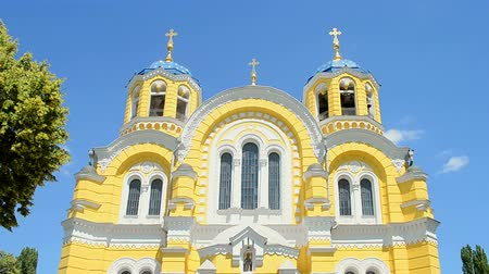 jesus born : KIEV, UKRAINE - JUN 08: St. Vladimir Cathedral aka Volodymyrsky Cathedral yellow stone building with blue sky and green park trees on June 08, 2018 in Kiev, Ukraine. It is place for Christian wedding, Easter and Sunday holiday ceremony for all christian p Stock Footage