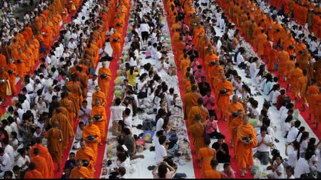 szerzetes : Monks are participating in a Mass Alms Giving of 12,600 monks in Saphan Khwai for the Makha Bucha celebrations in Bangkok, Thailand Stock mozgókép