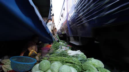 maeklong : TRAIN GOING THROUGH MARKET IN THAILAND
