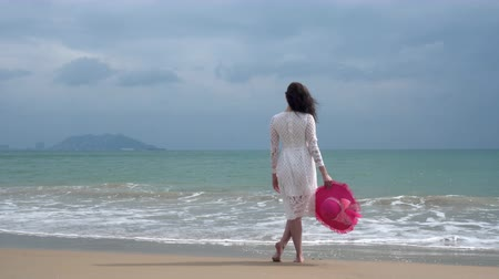 walking back : girl in a white dress and with a red hat is standing by the sea