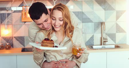 hugs : Happy cheerful loving couple, young attractive guy and girl standing in pajamas in the morning in the kitchen. Family life Stock Footage