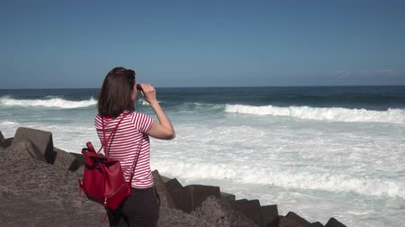 kanarya : girl hiker looking through binoculars on the Atlantic ocean Stok Video