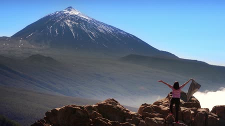 binocular : girl waves her jacket on the mountain next to the volcano