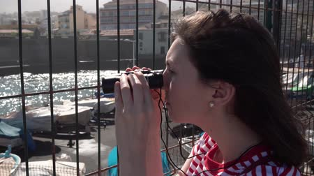 greenpeace : a journalist watching binoculars through the fence in Spain