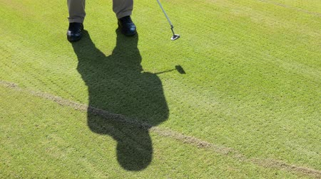 focus on foreground : the shadow of a man playing Golf on the grass. Ultra HD video